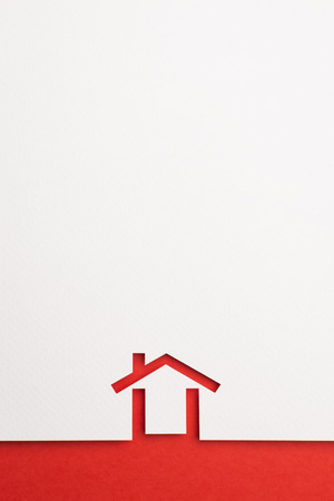 white paper cutout in minimal house shape with border background by red paper, for home and insurance conceptual. Banco de Imagens