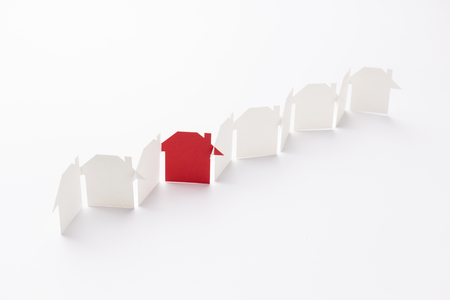 line linked of paper cutout houses with red one on white background, selective focused point, shallow depth of field. Stock Photo
