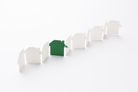 line linked of paper cutout houses with green one on white background, selective focused point, shallow depth of field.