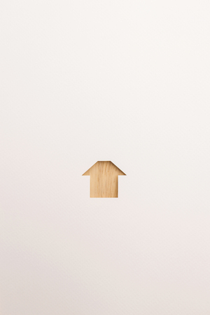 paper cutout in simple house shape by brown wooden textured on white paper background, for home and insurance conceptual.
