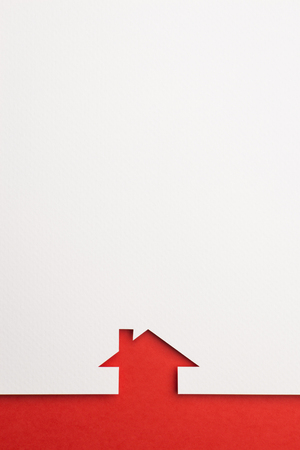 white paper cutout in simple house shape with border background by red paper, for home and insurance conceptual. Banco de Imagens