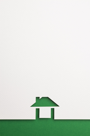 white paper cutout in easy house shape with border background by green paper, for home, ecology and energy conceptual.