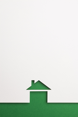 white paper cutout in basic house shape with border background by green paper, for home, ecology and energy conceptual.