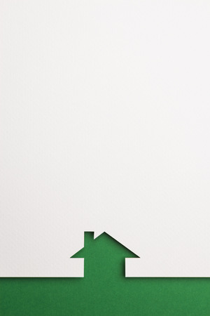 white paper cutout in simple house shape with border background by green paper, for home, ecology and energy conceptual. Banco de Imagens