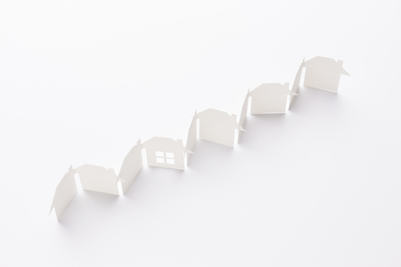 top view of line linked of paper cutout houses with detail one on white background Banco de Imagens