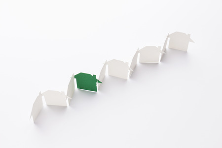 top view of line linked of paper cutout houses with green one on white background