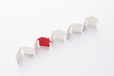 top view of line linked of paper cutout houses with red one on white background Banco de Imagens