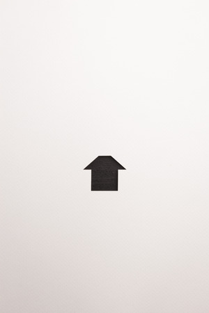 paper cutout in simple house shape by dark brown wooden textured on white paper background, for home and insurance conceptual. Banco de Imagens