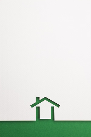 white paper cutout in minimal house shape with border background by green paper, for home, ecology and energy conceptual. Banco de Imagens