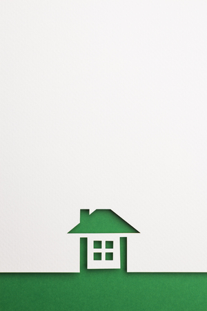 white paper cutout in complete house shape with border background by green paper, for home, ecology and energy conceptual.