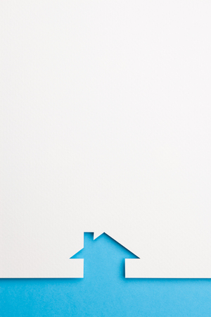 white paper cutout in simple house shape with border background by blue paper, for home and insurance conceptual.