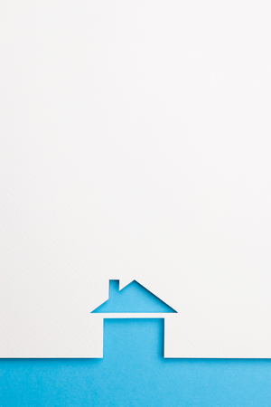 white paper cutout in basic house shape with border background by blue paper, for home and insurance conceptual.