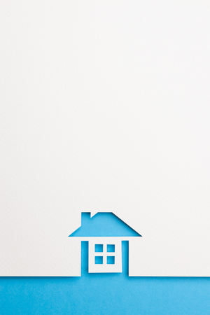 white paper cutout in complete house shape with border background by blue paper, for home and insurance conceptual. Banco de Imagens