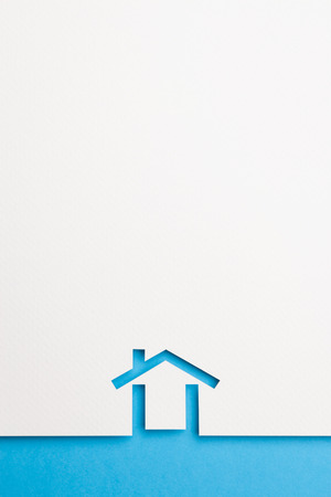 white paper cutout in minimal house shape with border background by blue paper, for home and insurance conceptual.