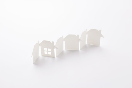 row linked of paper cutout houses with detail one on white background, for home and banking conceptual, selective focused.