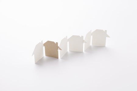 row linked of paper cutout houses with brown one on white background, for home  and ecology conceptual, selective focused. Stock Photo