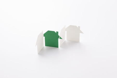 group linked of paper cutout houses with green one on white background, for home  and ecology conceptual, selective focused.