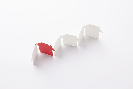 top view of row linked of paper cutout houses with red one on white background, for home and banking conceptual, selective focused. Stock Photo