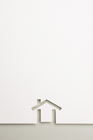 white paper cutout in minimal house shape with border background by gray paper, for home and insurance conceptual. Stock Photo