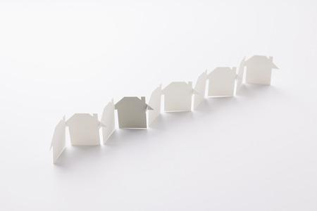 line linked of paper cutout houses with gray one on white background, for home and banking conceptual, selective focused.