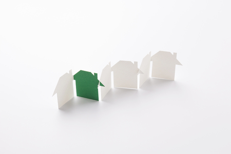 row linked of paper cutout houses with green one on white background, for home  and ecology conceptual, selective focused.