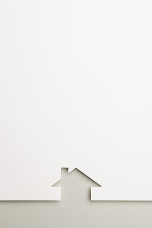 white paper cutout in simple house shape with border background by gray paper, for home and insurance conceptual. Banco de Imagens
