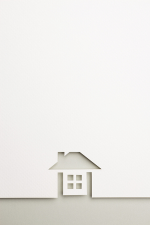 white paper cutout in complete house shape with border background by gray paper, for home and insurance conceptual. Banco de Imagens