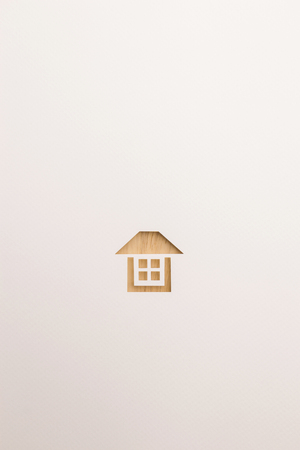 paper cutout in complete house shape by brown wooden textured on white paper background, for home and insurance conceptual.
