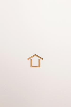 paper cutout in minimal house shape by brown wooden textured on white paper background, for home and insurance conceptual.