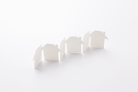 row linked of paper cutout houses on white background, for home and banking conceptual, selective focused.