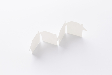 top view of group linked of paper cutout houses on white background, for home and banking conceptual, selective focused.