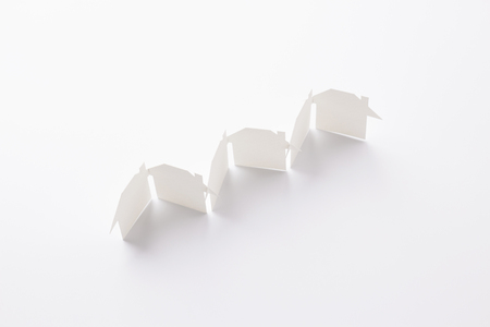 top view of row linked of paper cutout houses on white background, for home and banking conceptual, selective focused.
