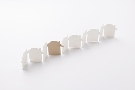 line linked of paper cutout houses with gray one on white background, for home and ecology conceptual, selective focused. Banco de Imagens