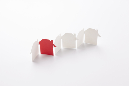 row linked of paper cutout houses with red one on white background, for home and banking conceptual, selective focused. Banco de Imagens