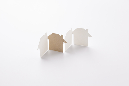 group linked of paper cutout houses with brown one on white background, for home and ecology conceptual, selective focused. Stock Photo