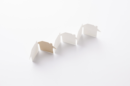 top view of row linked of paper cutout houses with brown one on white background, for home and ecology conceptual, selective focused.