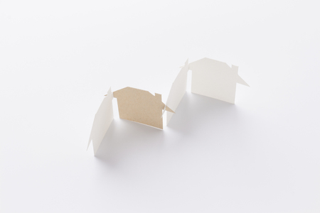 top view of group linked of paper cutout houses with brown one on white background, for home and ecology conceptual, selective focused.