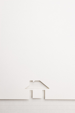 white paper cutout in easy house shape with border background by notepaper, for home and insurance conceptual.