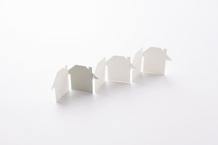 row linked of paper cutout houses with gray one on white background, for home and banking conceptual, selective focused. Banco de Imagens