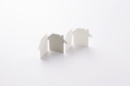 group linked of paper cutout houses with gray one on white background, for home and banking conceptual, selective focused. Banco de Imagens