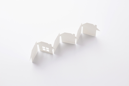 top view of row linked of paper cutout houses with detail one on white background, for home and banking conceptual, selective focused. Banco de Imagens