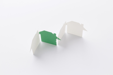 top view of group linked of paper cutout houses with green one on white background, for home and ecology conceptual, selective focused.