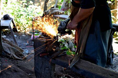 Closeup of a rudimentary iron working process, Cambodia