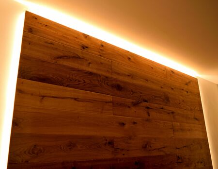 A closeup of a wall covered with parquet with its natural veins, delimited by LED strips.
