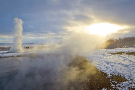 Konungshver steams towards the sun, while Strokkur geyser erupts in the background, in Iceland