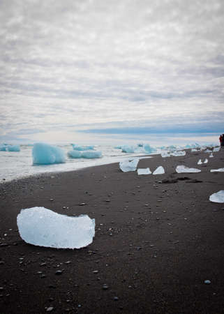 Tourists contemplate the icebergs from the nearby Vatnajokull glacier are washed up on the black beach of the south coast of Iceland, near Jokulsarlon.
