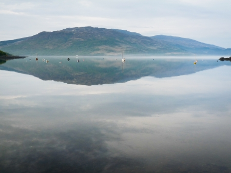 Mist over a still lake in the Isle of Skye photo