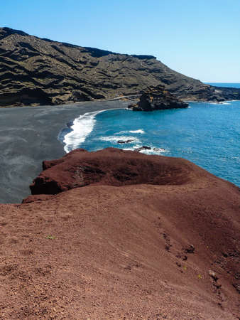 A red cliff down to the black beach at El Golfo, Lanzarote Stock Photo