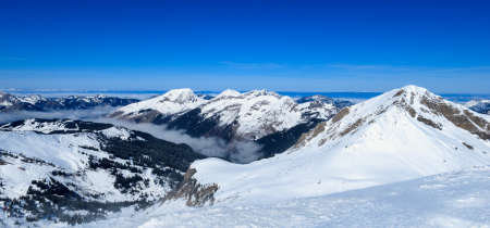 inversion: View over the snow covered French Alps, with a cloud inversion in a valley, a common sight in the ski fields