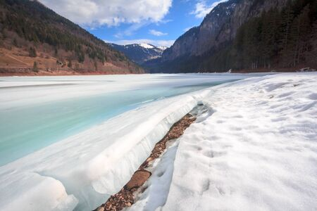Spring melt at the frozen lake at Lac du Montriond, in the French Alps Stock Photo